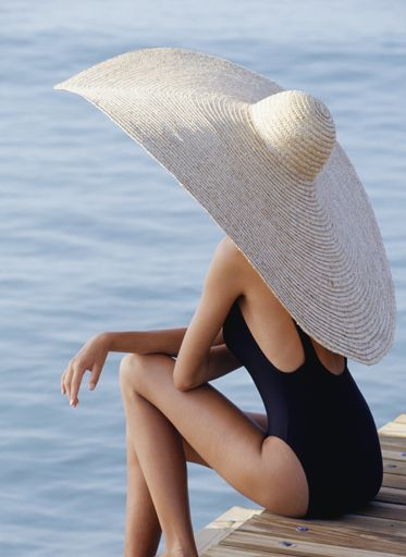 Woman in straw hat sitting on pier
